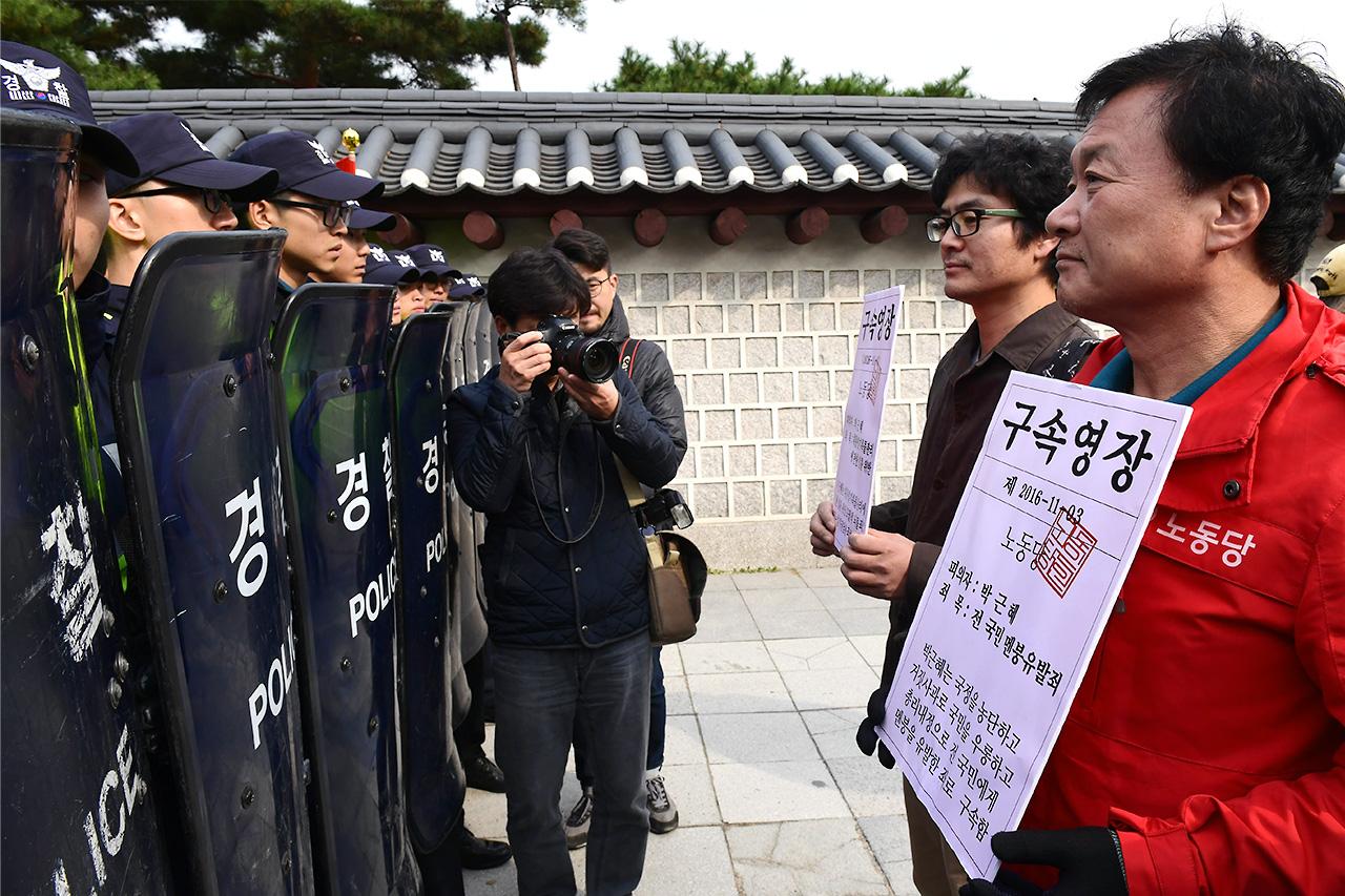 """노동당 당원들이 3일 오전 """"'박근혜 게이트'의 5대 주범인 청와대, 새누리당, 검찰, 재벌, 보수언론의 처벌'을 요구하며 청와대 방향으로 진출을 시도하자 경찰이 가로막고 있다."""