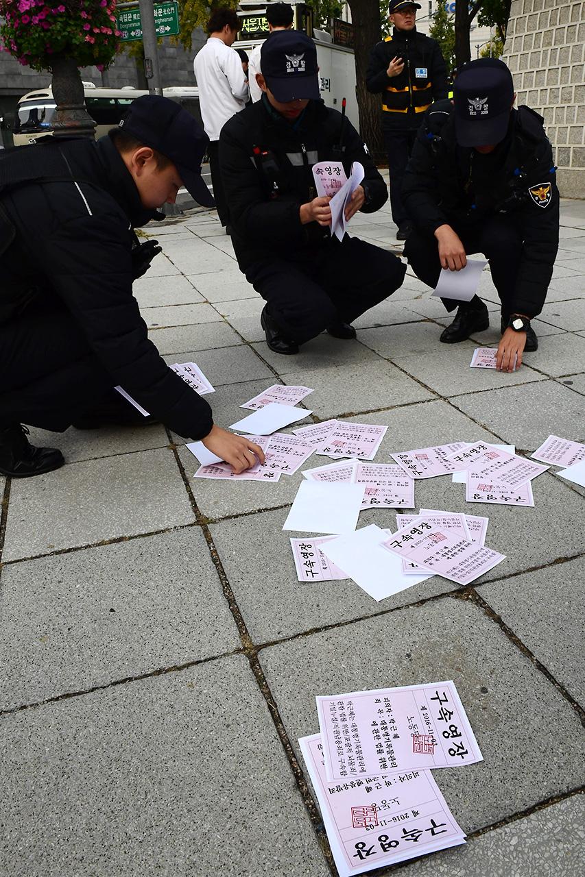 경찰들이 퍼포먼스에 사용된 '박근혜 구속영장' 유인물을 수거하고 있다.