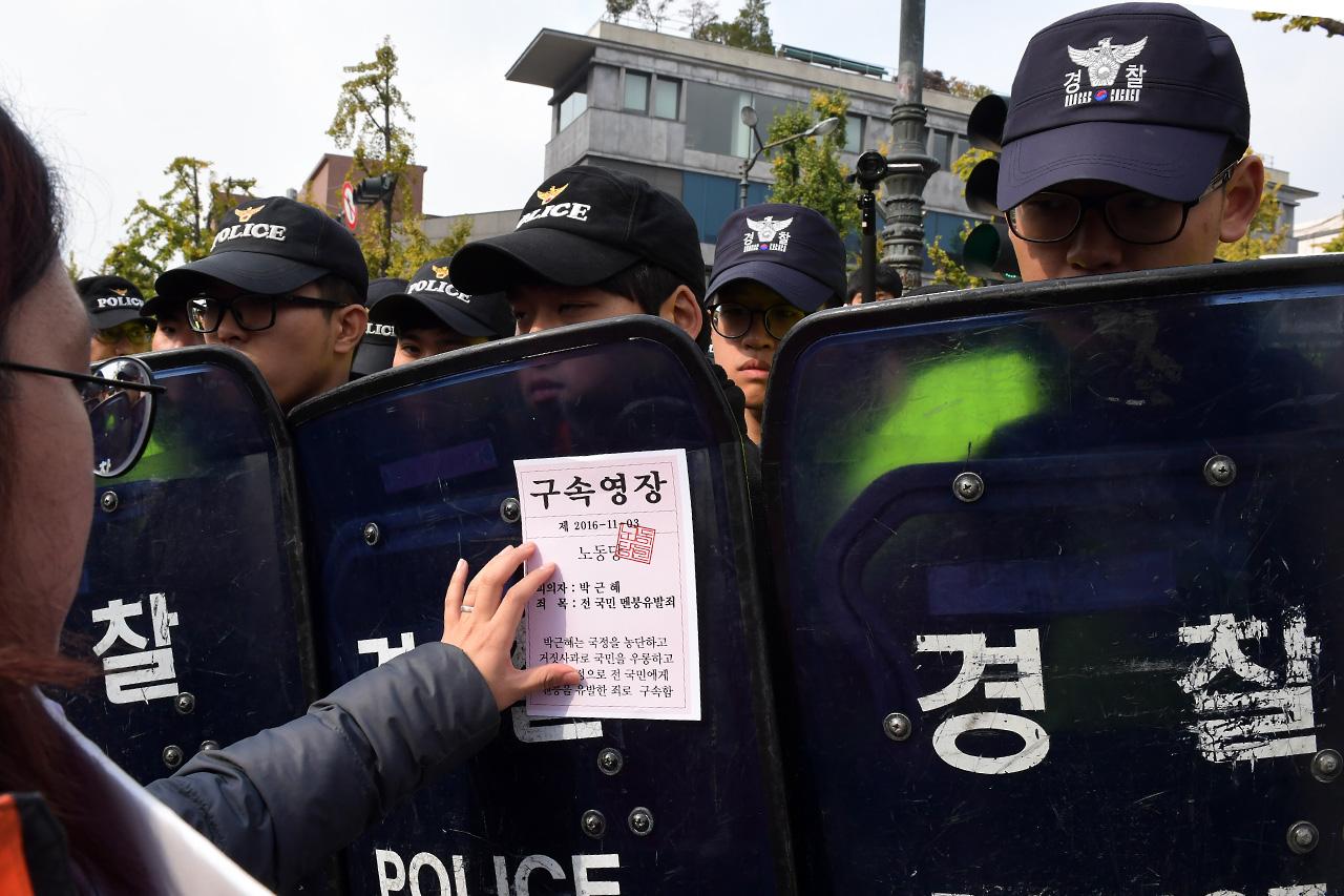 3일 오전 청와대로의 진출을 시도하던 노동당 당원들이 경찰에 가로막히자 '박근혜 구속영장' 유인물을 경찰의 방패에 붙이고 있다.