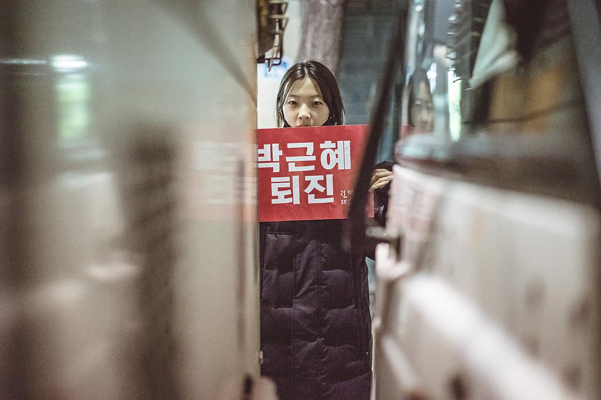 """[현장] 차벽넘어 외침 경복궁역 설치된 차벽 반대편에서 한 여학생이 """"박근혜 퇴진"""" 플래카드를 들고 있다."""
