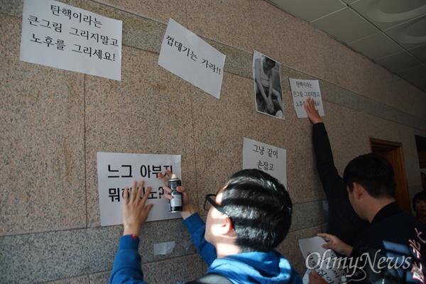 김무성 새누리당 전 대표가 15일 오후 경북대에서 열린 '4차 산업혁명과 지역경제 활성화 세미나'에 참석하기 전 학생들이 박근혜 탄핵과 새누리당 해체, 김무성 전 대표를 비판하는 A4 용지를 벽에 붙이고 있다.