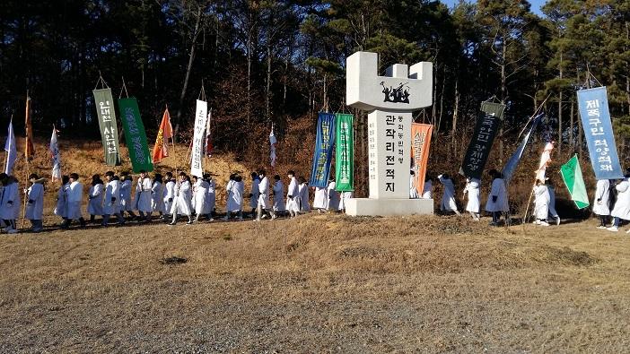 덕산고등학교 학생들이 예산농학혁명기념공원에서 동학혁명기념비 주변을 돌며 행진을 하고 있다.