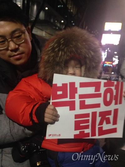 """3일 오후, 박근혜 대통령의 3차 대국민담화 이후 열린 첫 번째 촛불집회에 참석한 세 살배기 한시온군(3)과 아빠 한기영씨. 한씨는 """"우리 아들이 살 세상은 지금과 달랐으면, 국가를 신뢰할 수 있는 곳이었으면 좋겠다""""라고 말했다."""