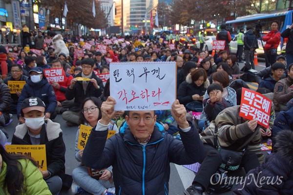 3일 오후 대구 한일로에서 열린 박근혜 퇴진 대구 시국대회에 참가한 한 시민이 '탄핵부결 각오하라'는 피켓을 들고 앉아 있다.