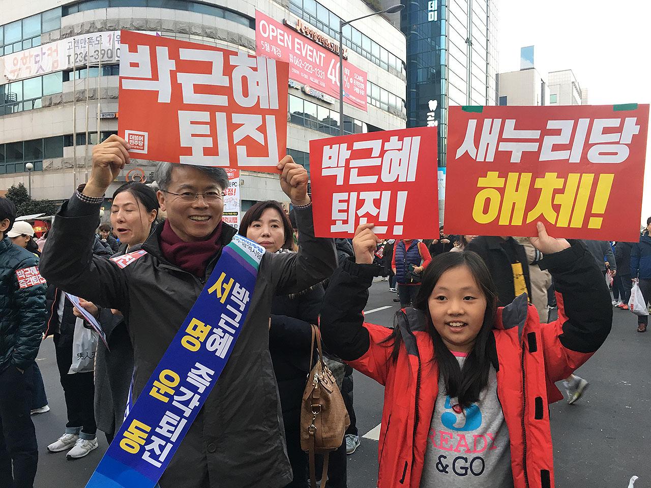 3일 오후 광주 금남로에서 '박근혜 퇴진' 서명운동을 하고 있던 민형배 광주 광산구청장이 아버지와 함께 시국촛불대회에 나온 김연경(초등3) 학생과 손 피켓을 들고 있다.