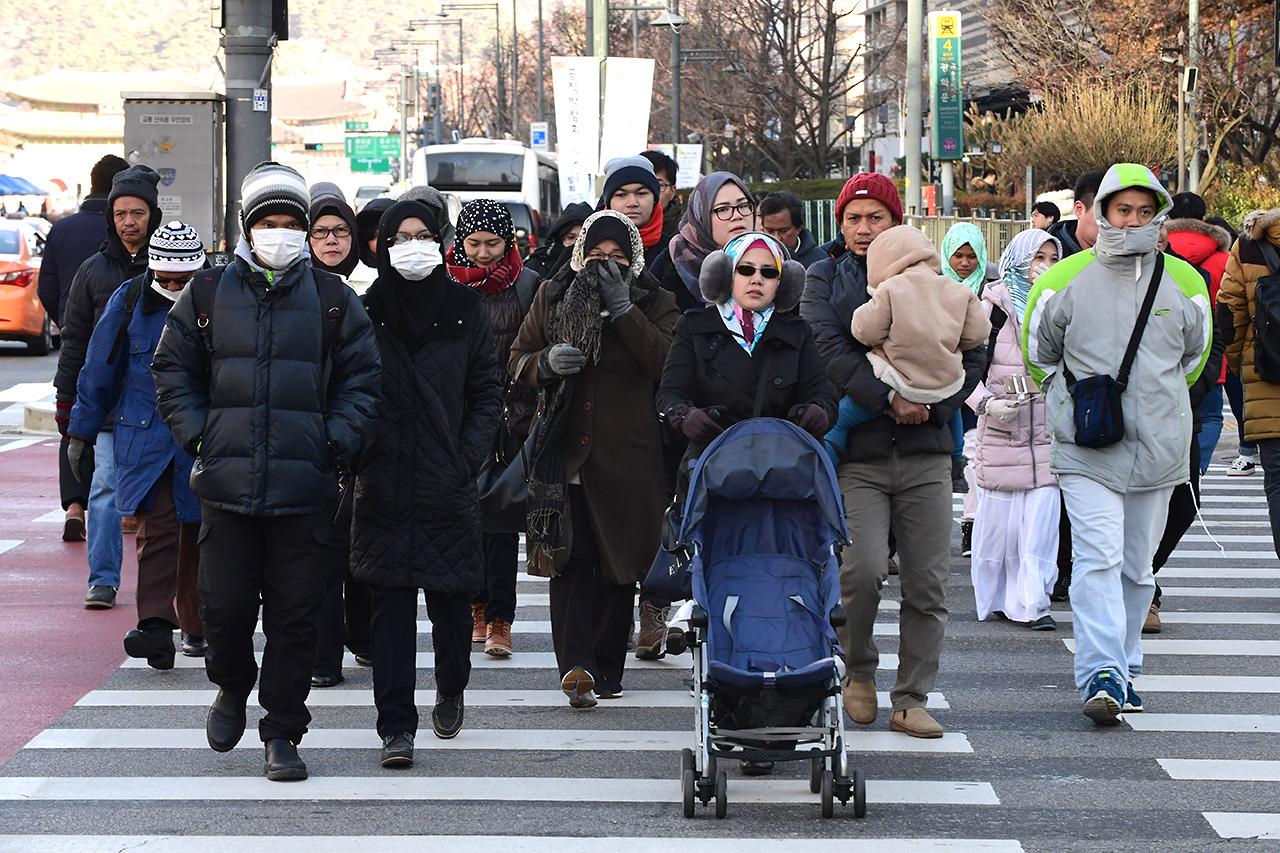 수도권에 한파주의보가 내려진 6일 오전, 외국인들이 두터운 옷을 입고 서울 광화문네거리 횡단보도를 건너고 있다.