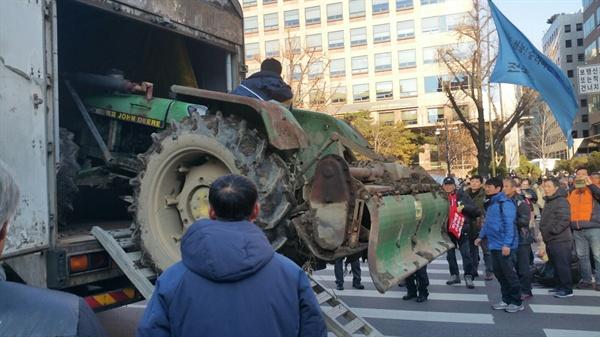 농민들이 화물탑차에 트랙터를 숨겨 국회 앞에 내려놓고 있다.