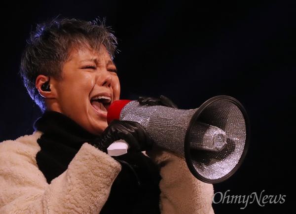 """광장에 선 이은미 """"당장 내려와라"""" 가수 이은미가 10일 서울 광화문광장에서 열린 7차 촛불집회에서 무대 공연을 펼치고 있다. '애국가'를 부르며 등장한 이은미는 """"국민의 명령이다, 지금 당장 내려와라""""라고 구호를 외쳐, 촛불을 든 시민들과 함께 '박근혜 즉각 퇴진'을 요구했다."""