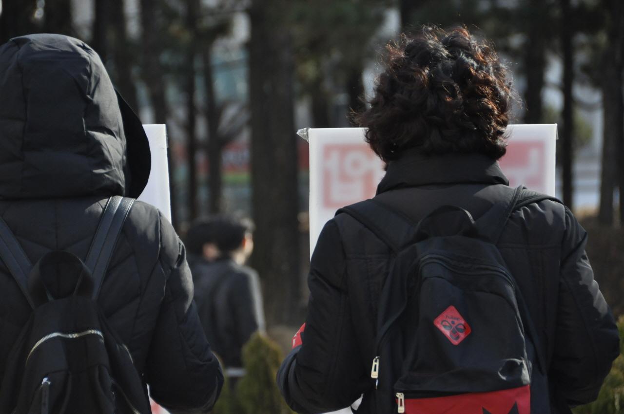 민주노총 서경지부 광운대분회 최수연 분회장이 지나가는 학생들을 바라보고 있다.