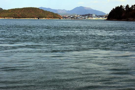 울돌목의 거센 물살이 진도 녹진항 앞을 흐르고 있다. 멀리 보이는 포구는 전라우수영이 있던 해남군 동외리로, 지금도 이 마을 955-6번지에는 명량대첩비가 남아 있다. 우수영 포구에서는 현대판 거북선을 타고 바다로 나아가는 체험을 할 수 있다.