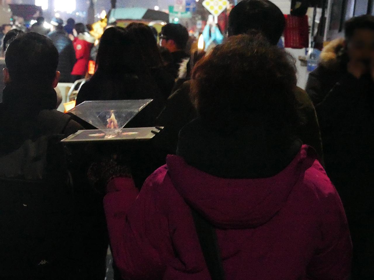 광화문에 나타난 홀로그램 촛불 한 시민이 홀로그램을 이용해 촛블을 들고있다