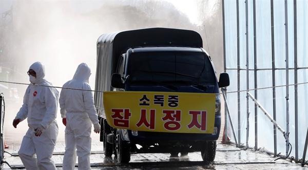 천안 닭·오리농장 3곳 AI 의심 신고가 들어온 지난 15일 천안 삼거리에 설치된 검점 소독시설에서 방역 관계자들이 차량 소독을 하고 있다.