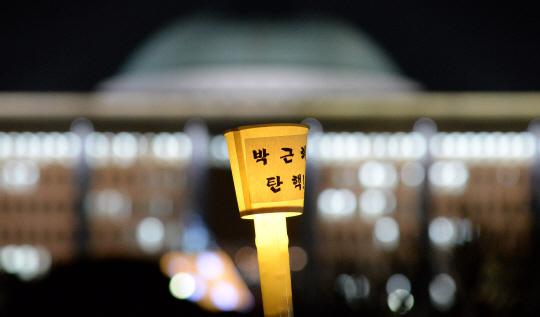 박근혜 대통령 탄핵소추안에 대한 국회의 표결을 앞두고 열린 국회 앞 촛불집회에서 한 시민이 든 '박근혜 탄핵'이라 적힌 촛불.