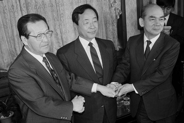 1990년 7월 당사에 출근한 김영삼 당시 민자당 대표가 김종필, 박태준 최고위원과 손을 맞잡은 모습.