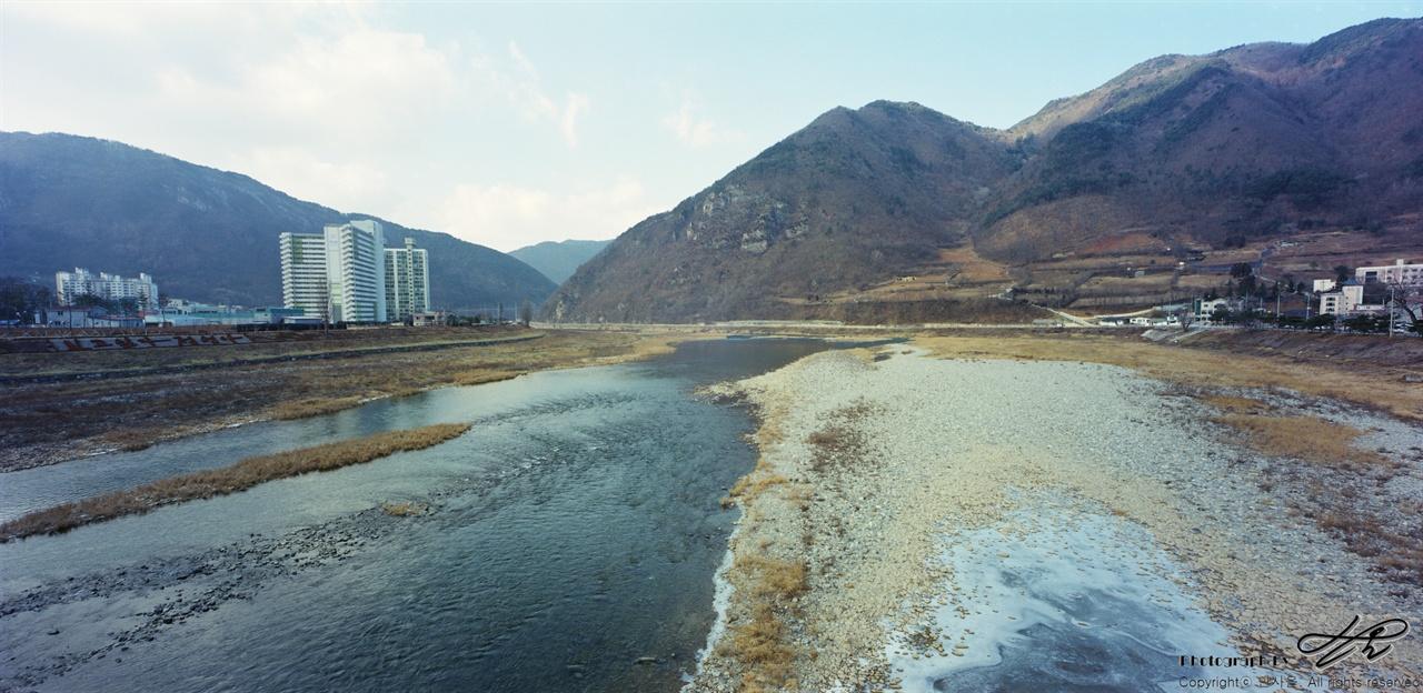 정선제1교 위에서 정선 읍내를 돌아나가는 동강의 모습. 다리 옆의 표지판에는 '한강'이라고 적혀있다. 렌즈의 각도 때문에 수면이 반사되어 물 속이 보이지 않는데 실제 눈으로는 바닥의 돌들이 훤히 보일만큼 물이 맑았다.(Portra400)