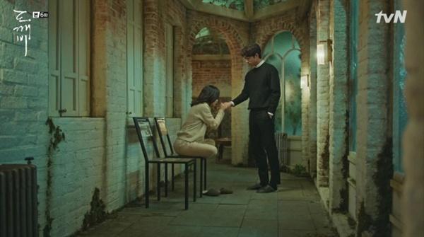 은탁이 김신의 손바닥에 '들을 청'을 적고 있다.