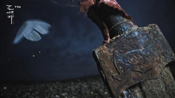 검 위를 날아다니는 흰색 나비 한 마리.