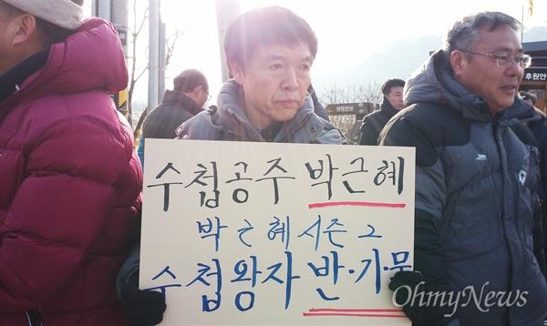 17일 아침, 봉하마을에서 한 시민이 '수첩공주 박근혜, 수첩왕자 반기문'이라고 적힌 피켓을 들고 있다.