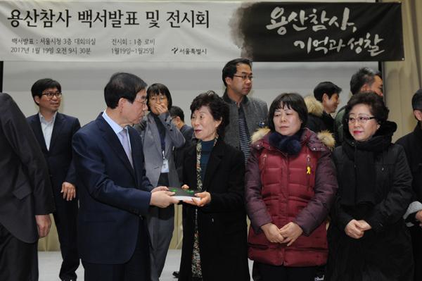 박원순 서울시장이 19일 오전 시청 대회의실에서 용산참사 유가족들에게 용산참사 백서를 전달하고 있다.