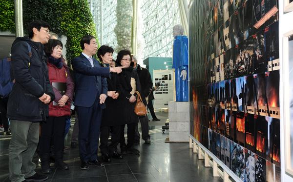 박원순 서울시장이 19일 오전 시청 로비에서 열린 용산참사 8주기 기념 전시회에서 유가족들과 함께 작품을 돌아보고 있다.