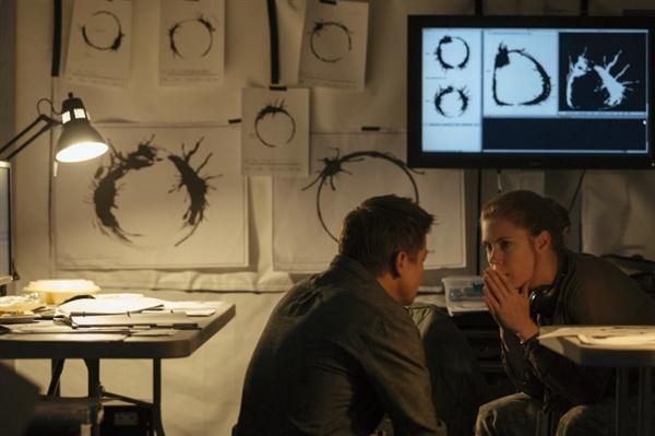 영화 <컨택트>의 한 장면. 루이스(에이미 아담스)와 그의 파트너 이안(제레미 레너)은 외계인들이 지구에 남기려고 한 메시지가 무엇인지 파악하기 위해 다각도로 헵타포드 문자를 연구한다.