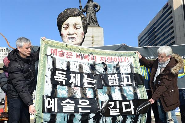 """문화연대를 비롯한 56개 문화예술단체 소속 관계자들이 6일 오전 서울 종로구 광화문광장에서 '창작 표현의 자유 수호와 <더러운 잠> 작품 훼손에 대한 예술인 기자회견'을 열고 최근 박근혜 대통령을 풍자한 <더러운 잠>을 훼손한 것에 대해 """"새누리당의 사과와 함께 보수단체 회원들의 법적 책임""""을 요구한 가운데 이진석 작가가 '독재는 짧고 예술은 길다'퍼포먼스를 펼치고 있다."""