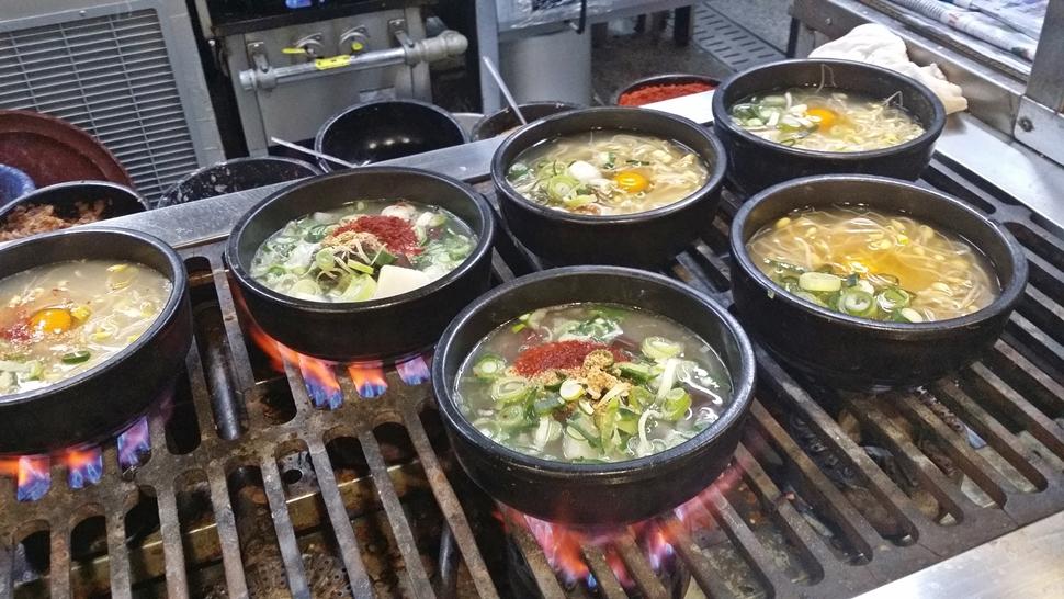 열린 주방의 가스 불 위에서 콩나물국밥이 설설 끓고 있다.