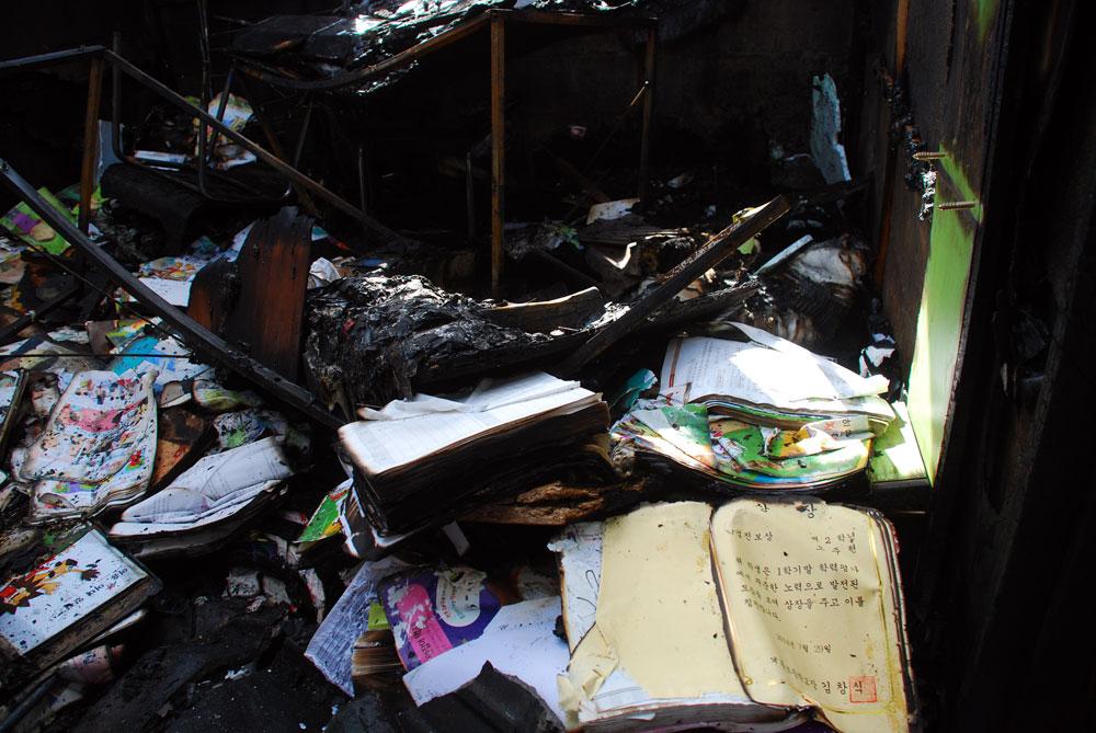 기왓장이 무너져 내린 사이에서 불에 타다만 연필과 공책, 상장을 찾았다.