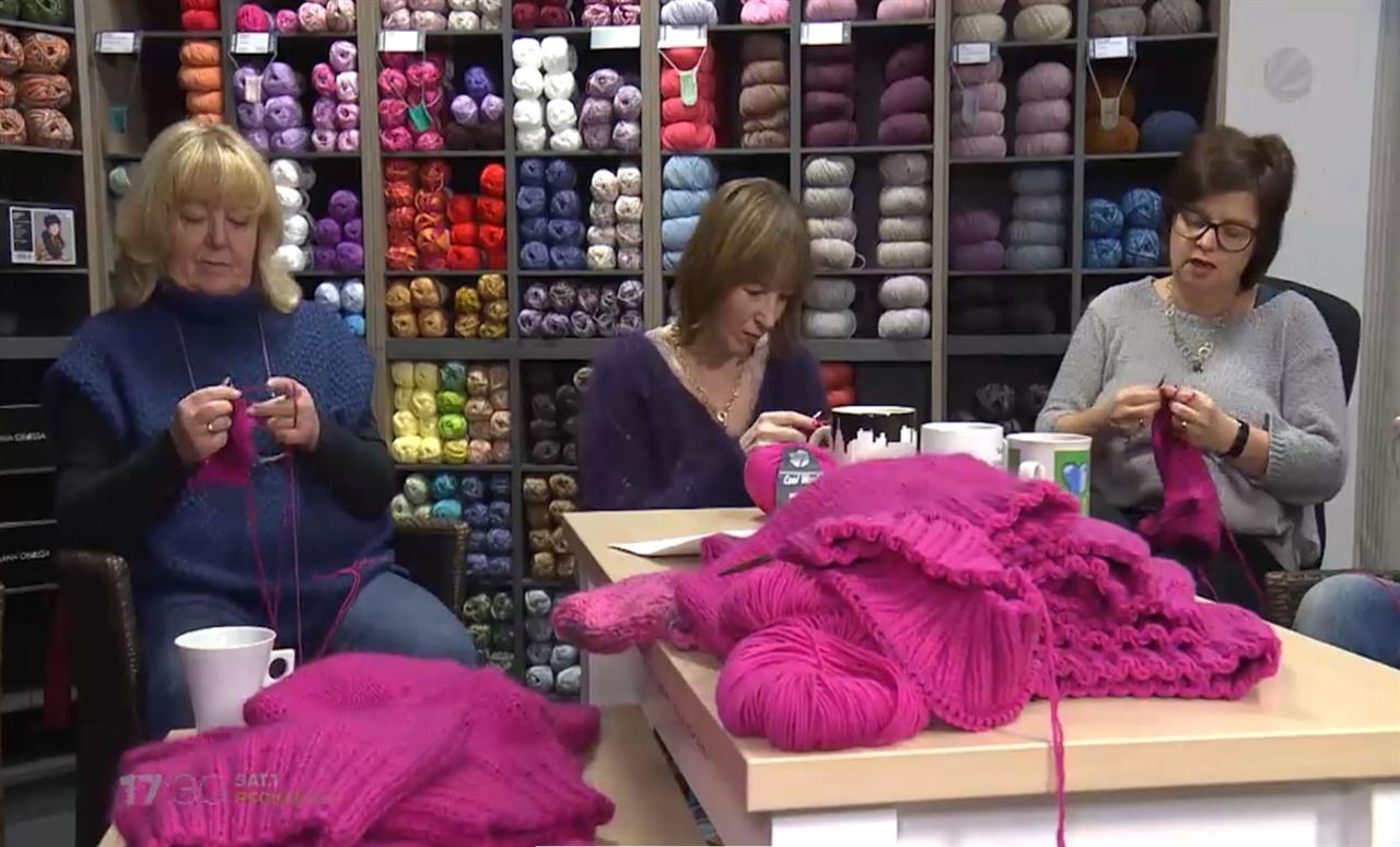 독일 여성들이 털실 가게에 모여 핑크색 모자를 뜨고 있는 모습