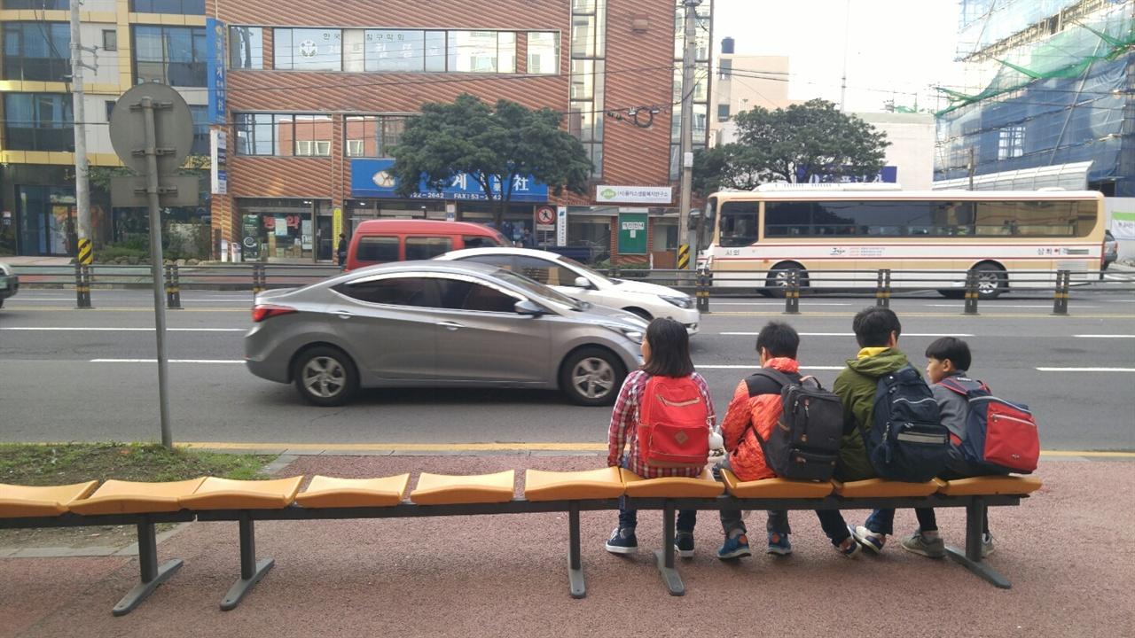 임시 버스정류장에서 서지 않는 버스를 기다리는 아이들