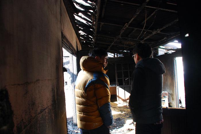 화재 소식을 듣고 찾아온 친구와 오산권씨가 불탄 집을 돌아보며 위로하고 있다.