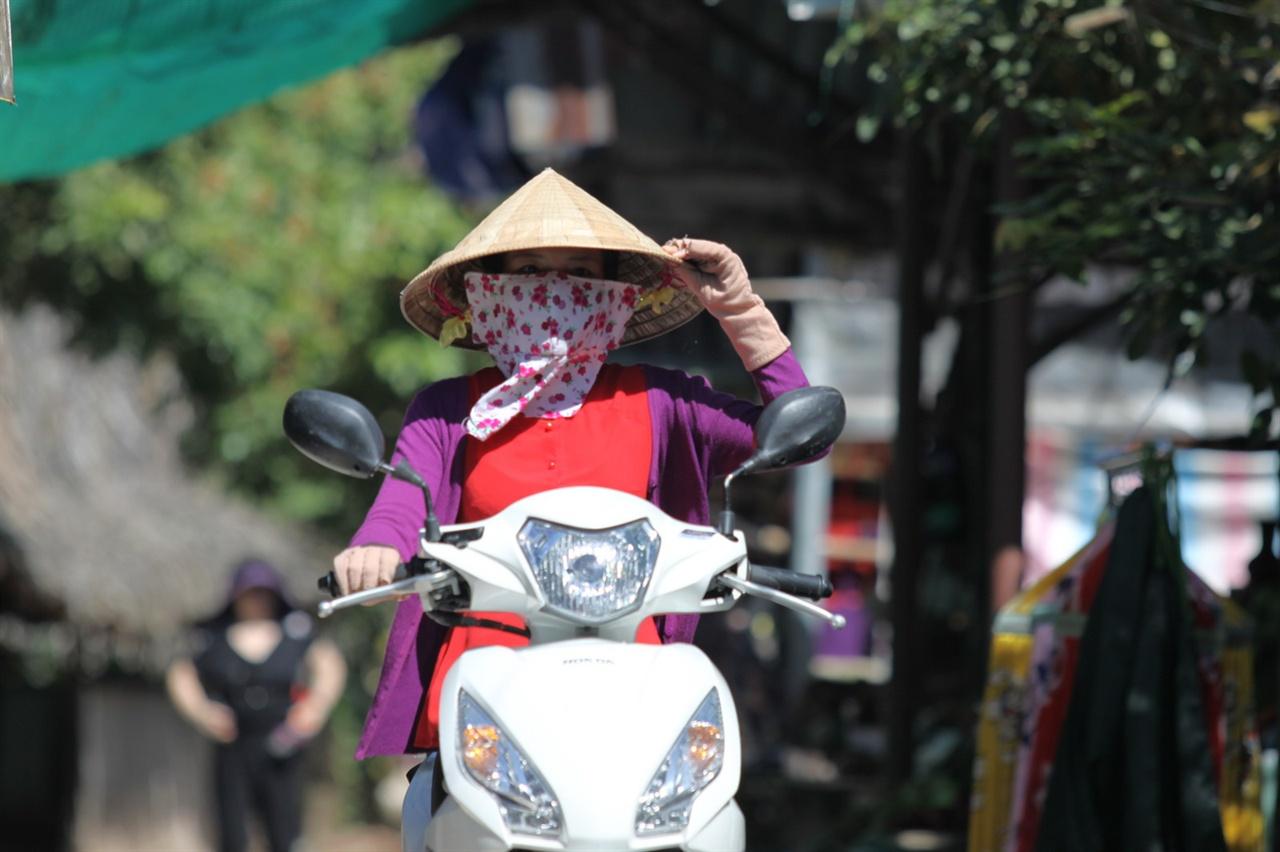 베트남 오토바이를 타고 이동하는 여성