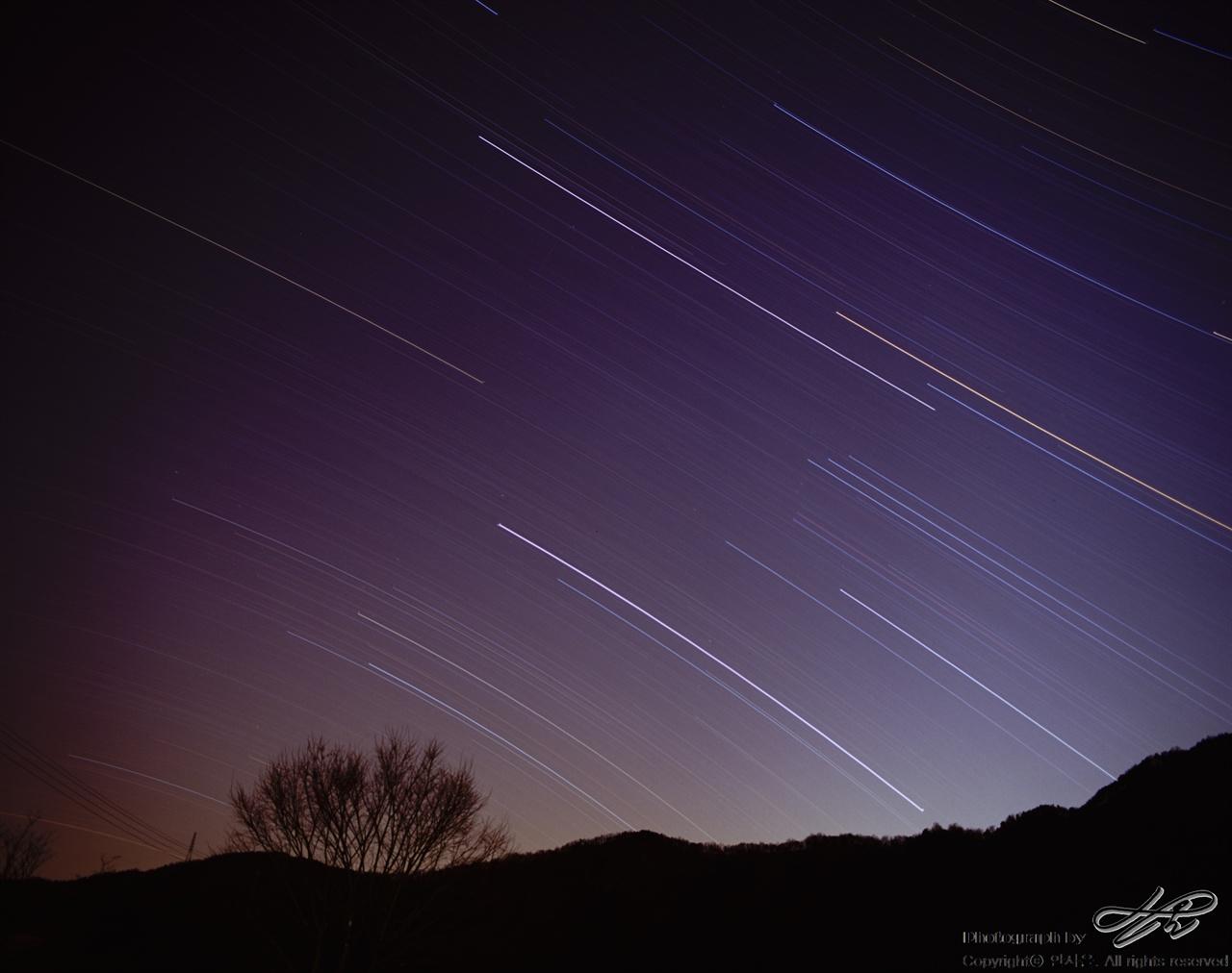 별의 이동(북서) 필름(PROVIA100F). 금강을 끼고 있는 산능선 위로 별들이 지나가고 있다. 두 시간 정도 렌즈를 열어두었다. 지구는 한 시간에 15도 자전한다.