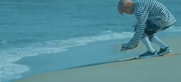 '봄날' 뮤직비디오에서 지민은 바닷가에 놓인 누군가의 신발을 집어든다.