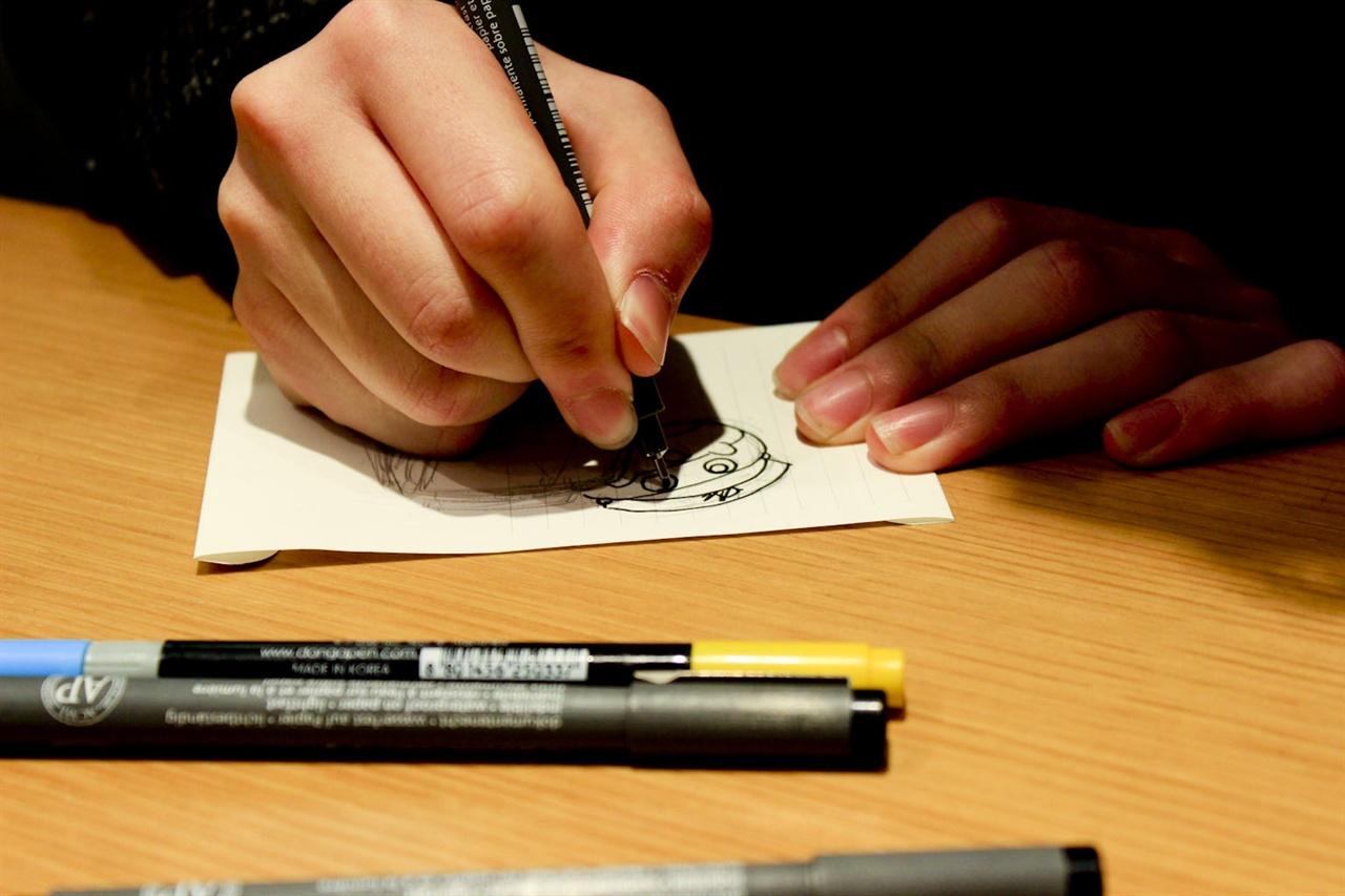 정경훈 씨가 인터뷰가 진행되는 중 자신의 오너 캐릭터인 '티오'와 열차를 모티브로 한 캐릭터를 그리고 있다.