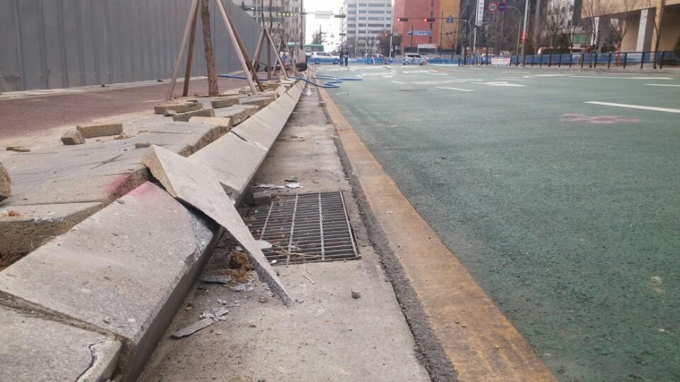 요진건설 공사장 앞 보행로. 보행로 벽돌이 떨어져 나가고, 도로와 보행목 사이에는 커다란 공간이 생겼다.