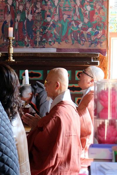 천은사 극락보전에서 법회 중인 흰 수염의 스님, 궁금증을 자극합니다.