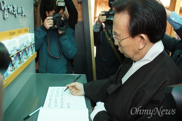 김관용 경상북도지사가 20일 오전 박정희 전 대통령 생가를 찾은 뒤 방명록에 글을 쓰고 있다.