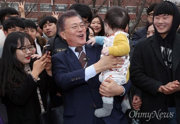 더불어민주당 대선주자로 나선 문재인 전 대표가 20일 광주 전남대를 방문해 한 지지자가 안긴 아이를 안고 있다.