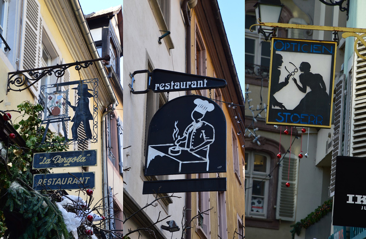 콜마르 가게들의 간판. 식당, 안경점 등의 가게에서 파는 물건들이 묘사되어 있다.
