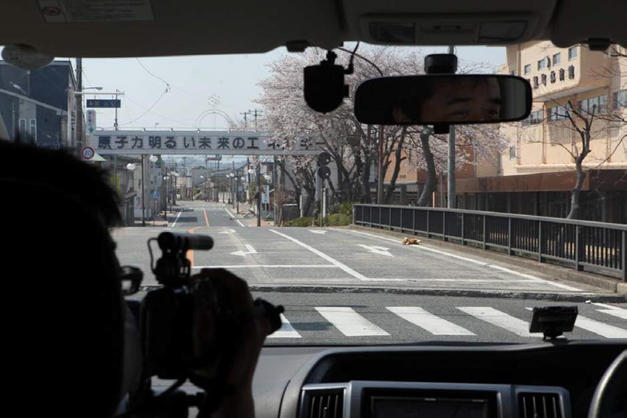 후쿠시마 원전이 있는 후타바마치 시가지, 사람이 남아있는 흔적을 전혀 찾을 수 없다. 도로위에 '원자력은 밝은 미래의 에너지'라고 쓰인 원전홍보선전물이 보인다.
