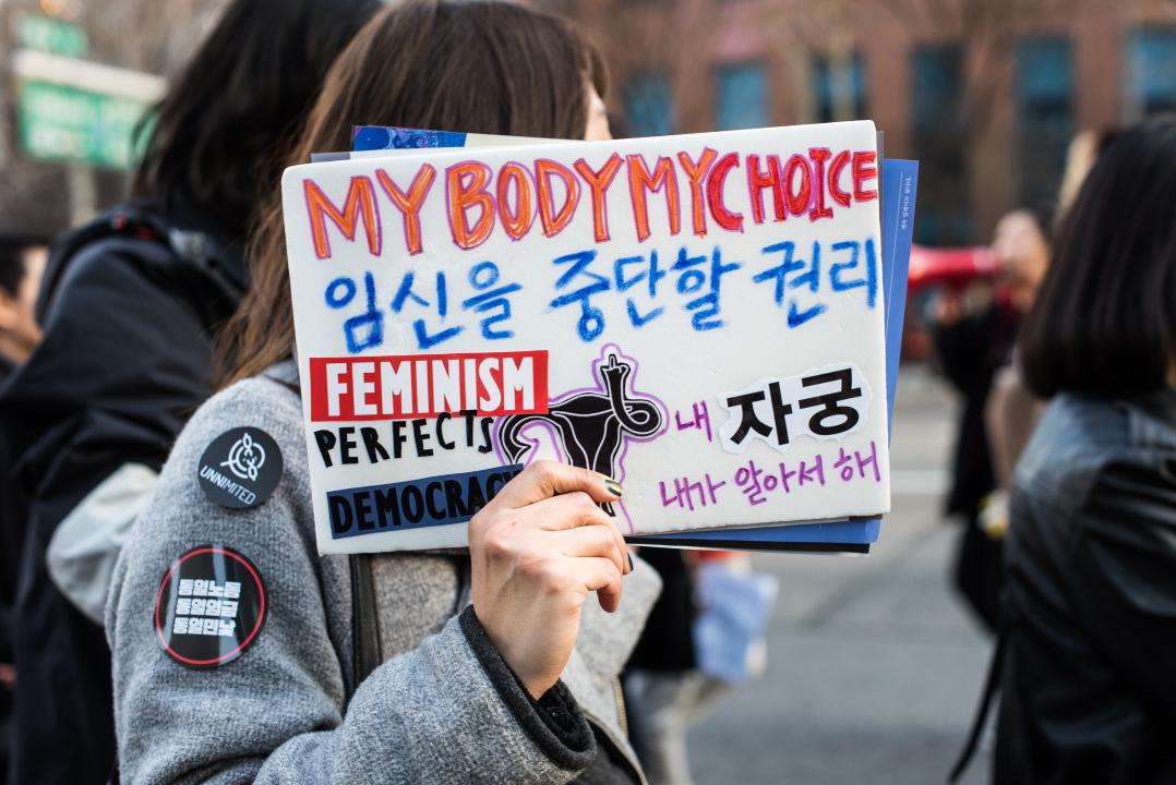 """2017년 3월 4일, '페미답게 쭉쭉간다' 3.8 여성의 날을 앞두고 청계광장에서 진행된 '페미답게 쭉쭉간다' 행진에서 한 참가자가 """"임신을 중단할 권리"""" 라고 적혀 있는 피켓을 들고 있다."""