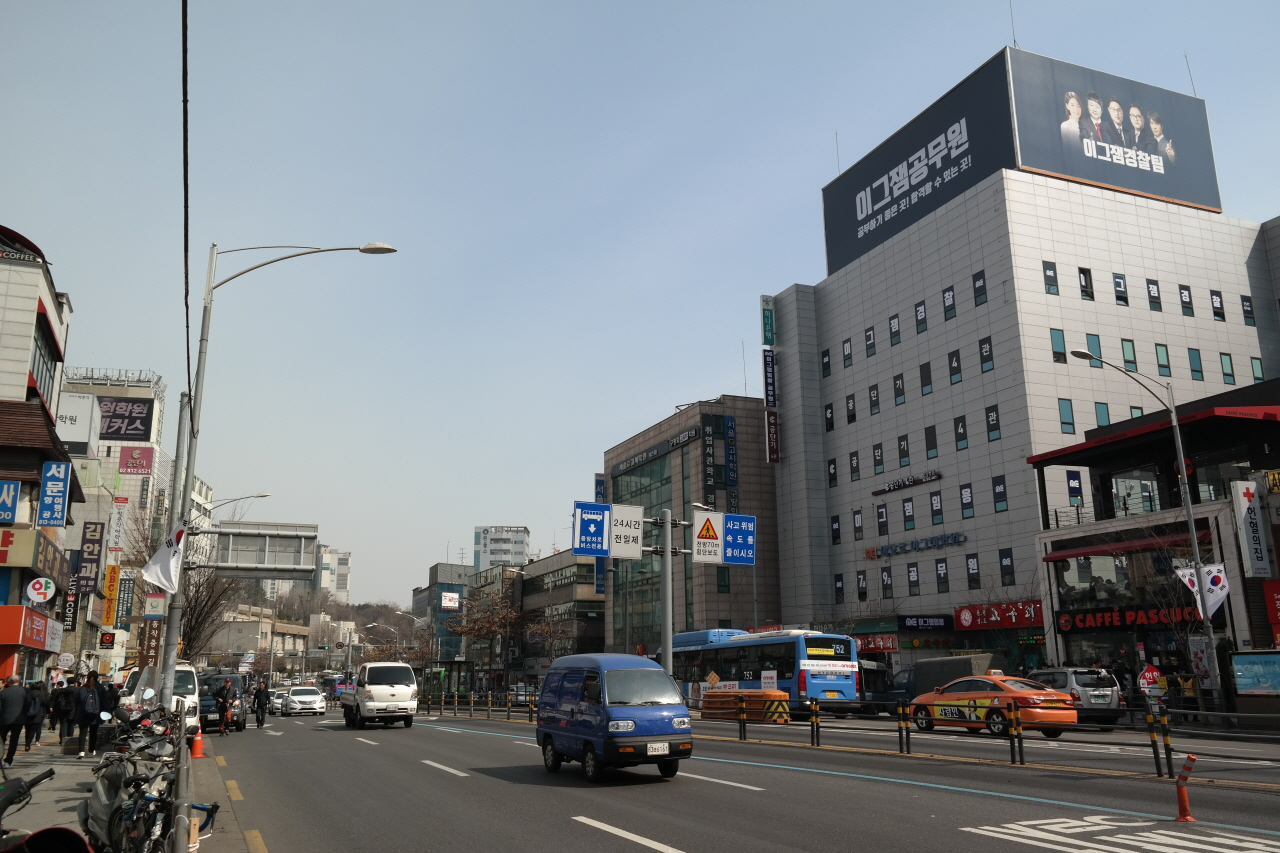 지난 3월 23일 오전 서울 지하철 1호선 노량진역 앞 도로에서 차들이 달리고 있다. 노변에는 공무원시험 준비학원 건물들이 성업 중이다.