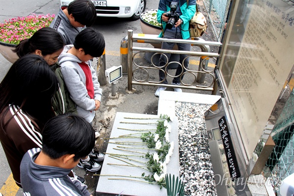 전북 남원 금지동초등학교 학생들이 11일 마산 김주열열사시신인양지 표지석 앞에 헌화한 뒤 묵념하고 있다.