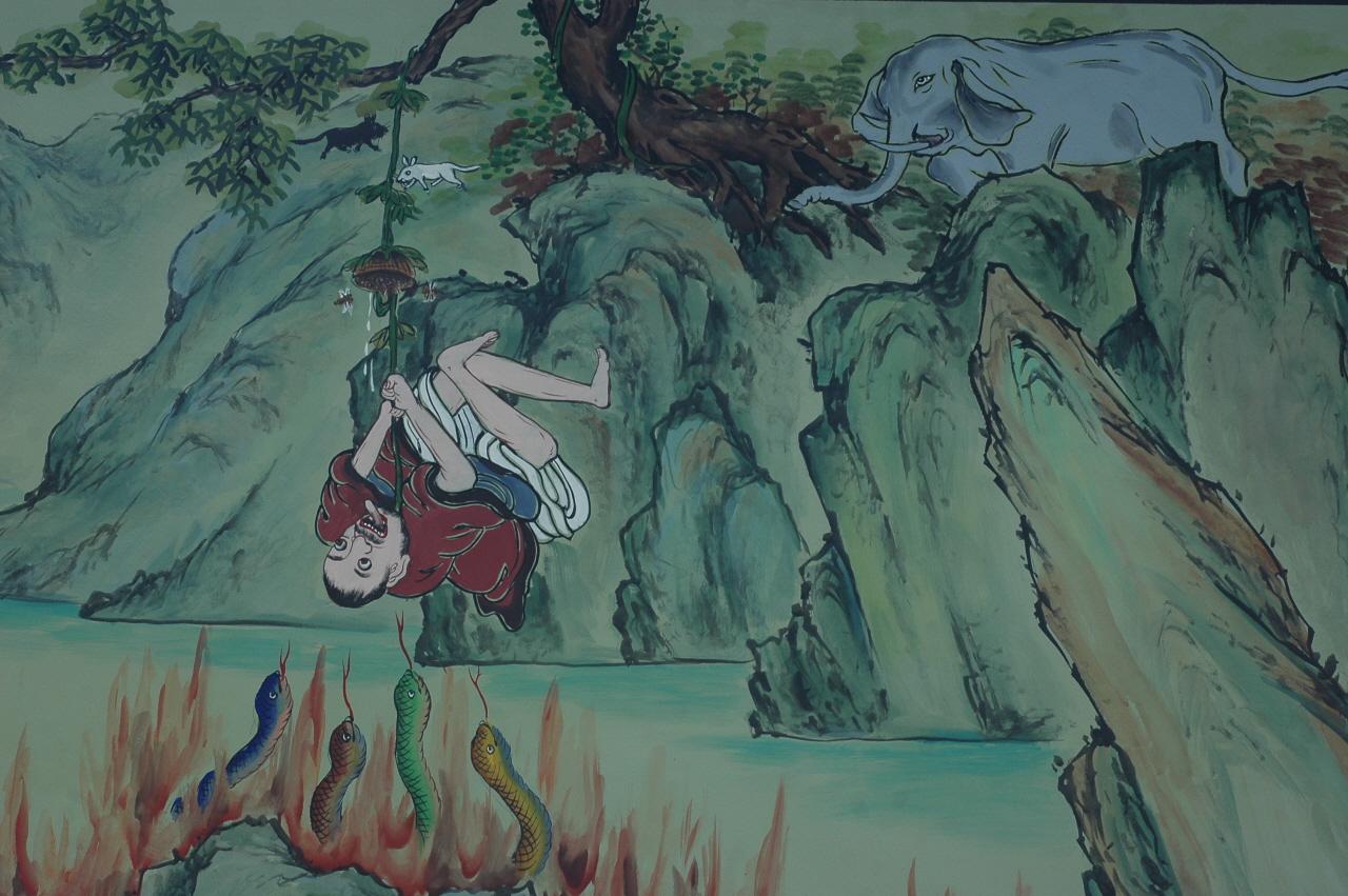 천장사 벽화. 절벽 위에서는 성난 코끼리가 쫒아오고 그 아래에는 독사들이 우글거리고 있는데 쥐들이 갉아 먹고 있는 나뭇가지에 대롱대롱 매달려 벌집에서 흘러나오는 꿀을 받아먹겠다고 입을 쩍 벌리고 있다.