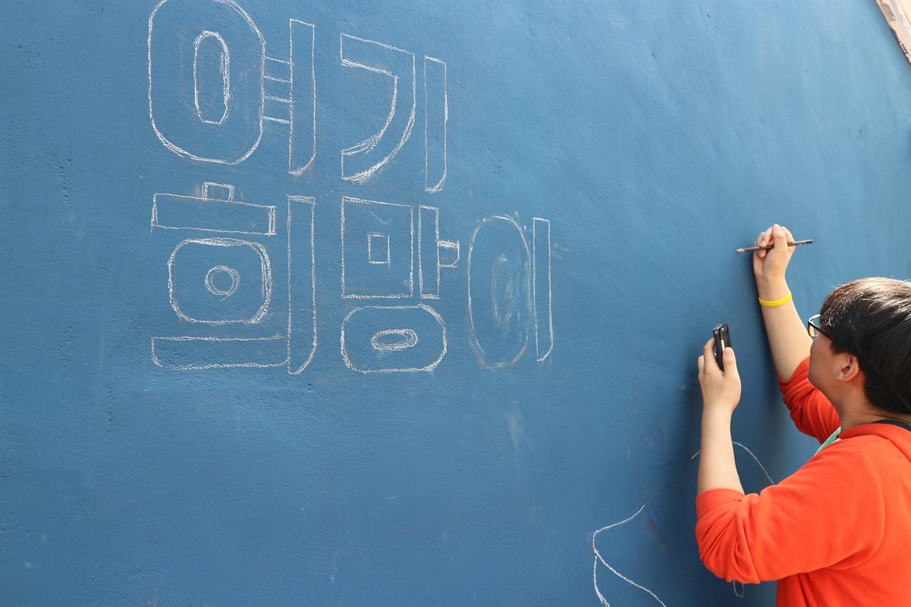강릉시 내곡동 골목 외벽에 첫 번째 벽화의 밑그림을 그리고 있다.