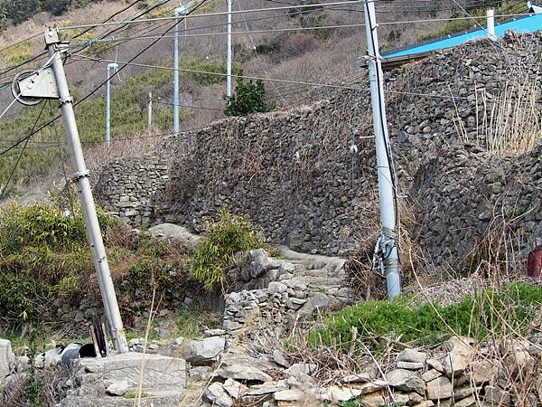 강풍을 막기위해 높은 돌담이 쳐진 집 모습. 태양광과 풍력을 이용해 발전하고 있지만 풍력발전기 2기 중 1기가 고장나있다