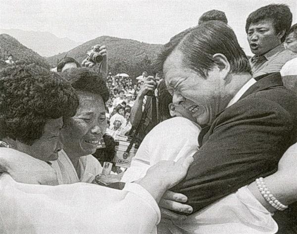 사진은 1987년 9월 8일 광주 망월동 묘역에서 김대중이 유가족과 함께 통곡하는 모습.