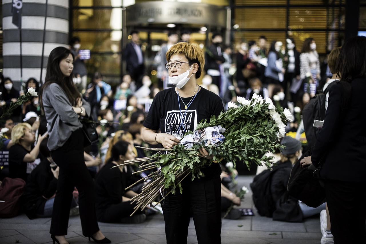 국화를 나눠 주고 있는 추모행진 스태프 5월 17일 강남역 10번출구 살인사건 1주기 추모행진 주최측이 참가자들에게 국화를 나눠주고 있다.