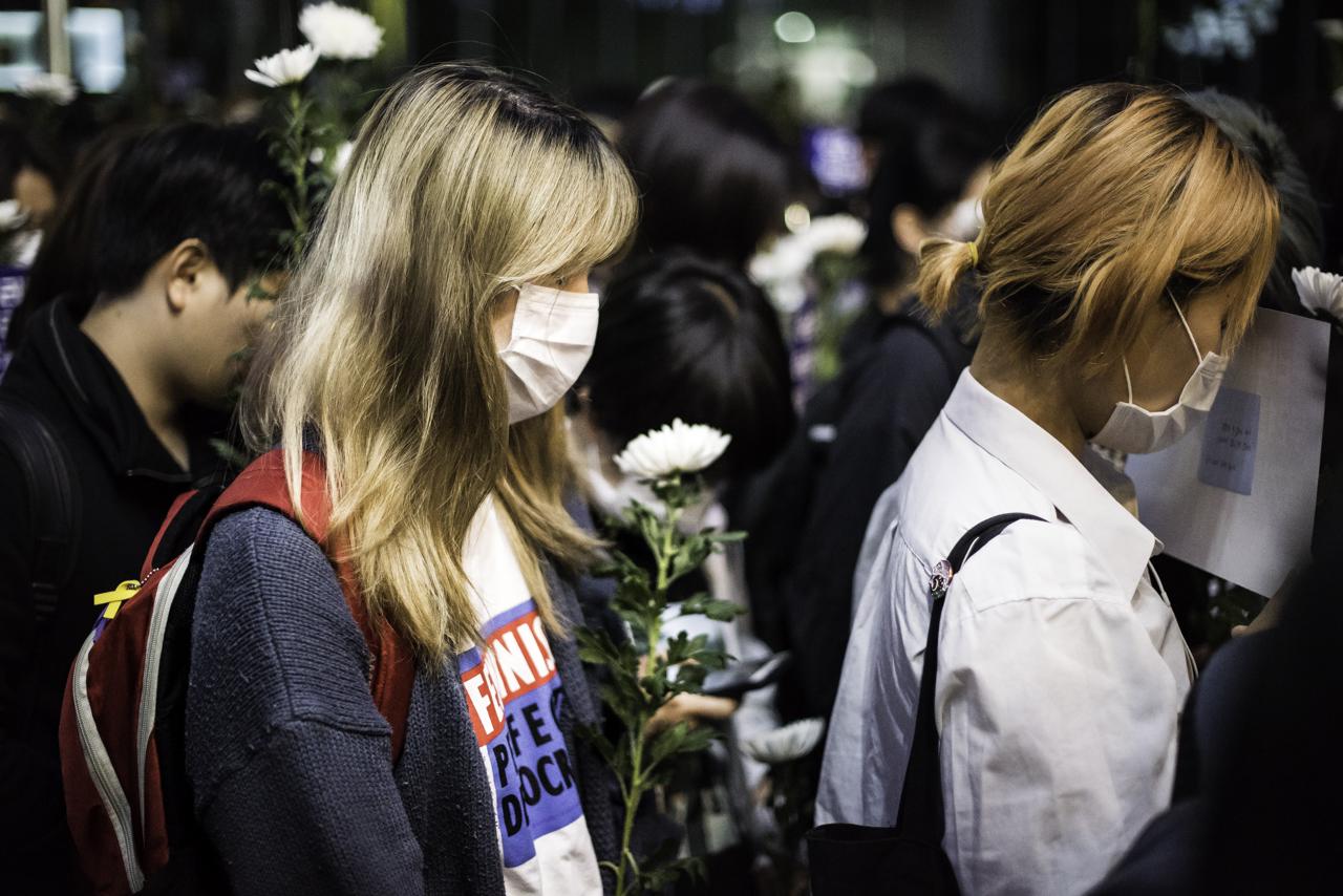 묵념을 하는 추모행진 참가자들 강남역 10번출구 살인사건 1주기 추모행진 참가자들이 사건이 일어난 건물 앞에서 묵념을 하고 있다.